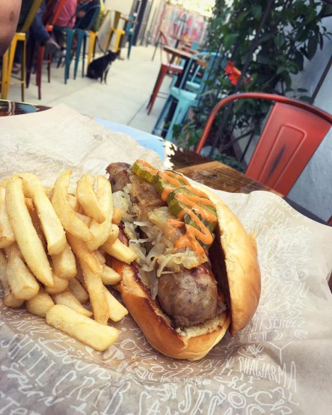 authentic-German-Bratwurst-accompanied-by-pickles-braised-sweet-onions-and-house-made-dark-beer-mustard.